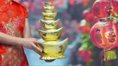 money thai : Woman holding Chinese new year gold ingots (qian) in chinatown