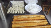 Çin yemek çubukları : Common breakfast foods in China , deep-fried dough sticks(youtiao),Rice noodles and dumplings on tray prepared for cooking