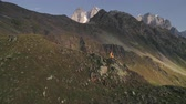 dolomity : Aerial slow-motion shot of a man climbing mountains on a sunny day in autumn. Dostupné videozáznamy