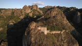 demolição : flying away from sharp rocks with little abandoned fortress in sunny evening