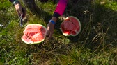 cooking : Man cutting watermelon into two halves with knife on the grass