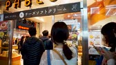 dotonbori : OSAKA, JAPAN - APRIL 30 : Japanese and tourists on the queue at PABLO at night ,  famous baked cheese cake and cheese tart store in Japan on April 30, 2017 in Osaka, Japan Stock Footage