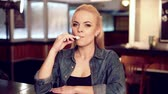 mod : Young pretty woman in smoke an electronic cigarette at the vape shop. Stock Footage
