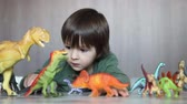 modelka : Adorable little boy, playing with plastic animals and dinosaurs on the floor