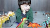сын : Adorable little boy, playing with plastic animals and dinosaurs on the floor