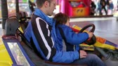 dostihy : Father and son riding on a colored electric cars in amusement park in action