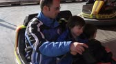 сын : Father and son riding on a colored electric cars in amusement park in action
