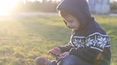 bebekler : Adorable little boy, playing on mobile phone on sunset, sitting on the grass Stok Video