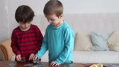 çözmek : Smart little boys, brothers, making puzzle at home during a weekend day Stok Video