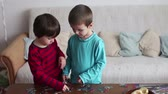 organizacja : Smart little boys, brothers, making puzzle at home during a weekend day Wideo
