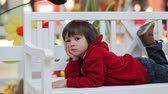 ver��o : Adorable little boy, lying on a bench, smiling at the camera