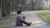 évjárat : Cute little toddler boy, with suitcase and teddy bear in the park on sunset, having fun outdoor