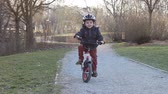 outdoor pursuit : Boy riding a bicycle in a  park,  concept for healthy lifestyle, exercising and road safety Stock Footage