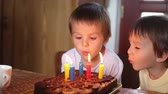 свеча : Adorable five year old boy celebrating his birthday and blowing candles Стоковые видеозаписи