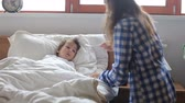 mamãe : Sick boy, lying in bed, mother checking his temperature and giving him medicine