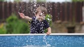 игривый : Little boy, splashing water from a pool, laughing