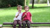 spiral : Adorable boys, licking lollipops outside on a sunny day