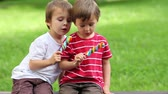 кондитерские изделия : Adorable boys, licking lollipops outside on a sunny day