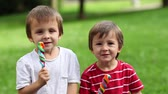 circo : Adorable boys, licking lollipops outside on a sunny day
