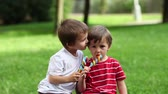 arco íris : Adorable boys, licking lollipops outside on a sunny day