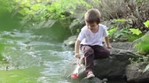 seyahat : Little boy playing with wooden boat by a river on spring or autumn day. Creative leisure with kids Stok Video