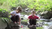 de madeira : Two little brothers playing together with wooden boat by a river on spring or autumn day. Creative leisure with kids
