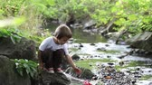 ship : Little boy playing with wooden boat by a river on spring or autumn day. Creative leisure with kids Stock Footage