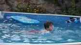 estouro : Cute little boy, swimming in a pool in the summer, having fun