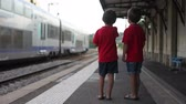 ferrovia : Two boys, watching a train leaving a station Stock Footage