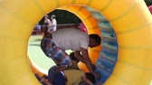 criança : Father and two sons, having fun in a big rolling spherical ring, zorbing