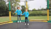 jumping : Little children jumping on big garden trampoline Stock Footage
