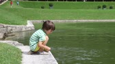 rybník : Cute little boy feeding fishes in the pond in a park