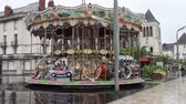 roundabout : Merry-Go-Round carousel on a rainy day, reflection on the pavement, France