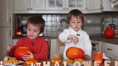 criança : Two kids, cutting pumpkins for Halloween