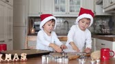foods : Two kids preparing christmas cookies and put them on baking tray together