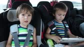 смех : Happy little boys playing game on tablet and playing with toys, while sitting in child safety seat in the car