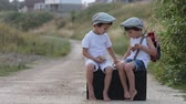клещи : Two boys, sitting on a big old vintage suitcase, playing with toys and eating bread