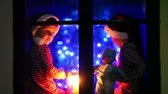 göksel : Two children, boys, sitting on a window at night, one holding toy, other playing on phone, waiting for Christmas, colorful tree behind them