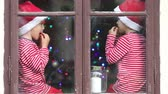 geléia : Two cute boys, brothers looking through a window, eating gummy bears, waiting for Santa Vídeos