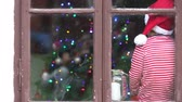 little : Two children, boys, sitting on a window daytime, waiting impatiently for Christmas, colorful tree behind them