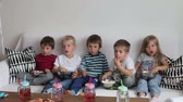 сидящий : Five sweet kids, friends, sitting in living room at home, watching TV and eating popcorn Стоковые видеозаписи
