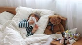 doku : Sick child boy lying in bed with a fever,resting, coughing and blowing his nose