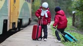 hat : Two cute boys on railway with suitcases, running after a train, autumn time