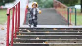 chovendo : Little boy, jumping in muddy puddles in the park, going down stairs