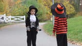 magik : Two boys in the park with Halloween costumes, having fun Wideo