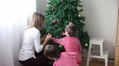 três pessoas : Two boys and their mother, decorating Christmas tree