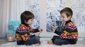 cartão de natal : Two adorable children, boy brothers, playing cards at home, wintertime, christmas decoration around them, snowy day behind the window