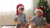 at home : Two cute children, preparing gingerbread cookies for Christmas