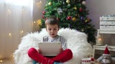 gripe : Cute boy, sitting on bean bag, drinking tea and enjoying Christmas holidays, Christmas decoration around him