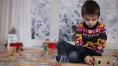 trilho : Adorable little preschool boy, playing with wooden trains and railroad at home, wintertime